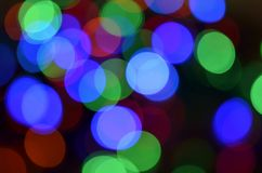 Abstract Light Bokeh Background. Colored bokeh Christmas garland.Christmas and New Year Garland Design black Background Royalty Free Stock Photos
