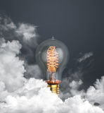 Abstract light bulb glowing on dark grey background with clouds Stock Images