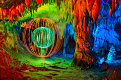 Abstract Light Painting. Cave interior abstract painted with colored light and a double sphere made with light on one side stock photo