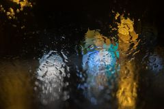 Abstract lights blue, yellow and white color on a black background. Blurred glare of light yellow, white, blue on the glass. Abstract blots of light spots stock image