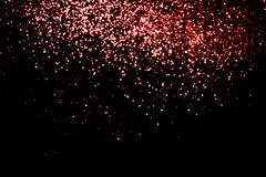 Abstract living coral bokeh texture on black background. Defocused sparkles. Color of the year stock images