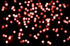Abstract living coral bokeh texture on black background. Defocused sparkles. Color of the year stock photo