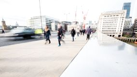 Abstract London commuters. LONDON, UK - 1 APRIL 2016: Commuters and office workers crossing London Bridge during their rush hour commute. Deliberate high key Stock Image
