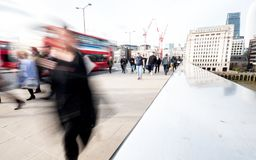 Abstract London commuters. LONDON, UK - 1 APRIL 2016: Commuters and office workers crossing London Bridge during their rush hour commute. Deliberate high key Stock Photo