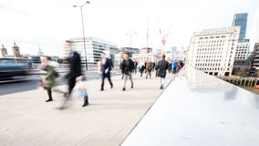 Abstract London commuters. LONDON, UK - 1 APRIL 2016: Commuters and office workers crossing London Bridge during their rush hour commute. Deliberate high key Royalty Free Stock Photo