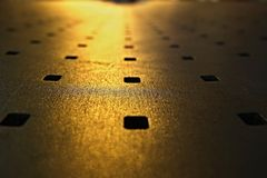 Abstract look of metal bench. With yellow night light royalty free stock images