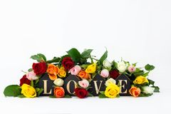 Abstract love concept with word love and colorful roses on white background. Creative romantic wedding card with copy space stock images