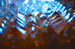 Close up of cut crystal facets in mysterios cold blue light. Abstract magic shiny blurred blue background royalty free stock photography