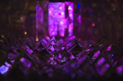 Close up of crystal facets in mysterious violet light. Abstract magic shiny blurred violet background stock photo