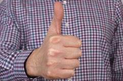 Abstract man in check shirt showing ok sign. Close shot of man in check shirt showing ok sign with his right hand Stock Image