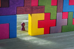 Abstract man in the doorway. Colorful wall of wooden puzzles. Construction of geometrik shapes Stock Photography