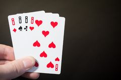 Abstract: man hand holding playing card four eight isolated on black background with copyspace poker set four eight. Close up shot Royalty Free Stock Photography