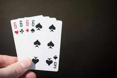 Abstract: man hand holding playing card four six isolated on black background with copyspace poker set four six Stock Photos