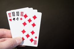 Abstract: man hand holding playing card four Ten isolated on black background with copyspace Royalty Free Stock Photos