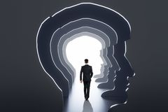 Abstract man head corridor. Back view of businessman walking in abstract man head corridor with light. Abstraction and way concept stock images