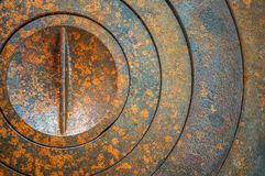Abstract metal background with geometric holes in a circle and rust texture orange-brown with spots. Selective focus.  royalty free stock photo