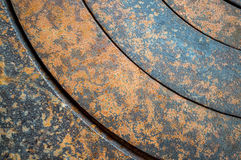 Abstract metal background with geometric holes in a circle and texture rust orange-brown with spots. The horizontal. Abstract metal background with geometric royalty free stock image