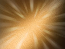 Abstract Metal Bronze Background. A bronze metal surface with a brushed texture and beams of light Royalty Free Stock Images