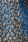 Abstract metal chain links on blue background. Abstract silver metal chain links on blue background. Industrial modern texture. Selective focus, shallow DOF stock image