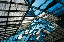 Abstract metal construction of roof with glass window. Modern gray construction of roof with blue windows royalty free stock photography