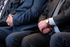 Male hands closeup. Abstract middle-aged men in a suit of an official or a businessman at a meeting. Wristwatches, shirt, tie. stock photo