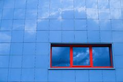Abstract minimalism wall constructed with blue squares and three red windows on it stock photos