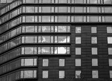Abstract modern office house facade with windows on sky reflection. Black and white Royalty Free Stock Images