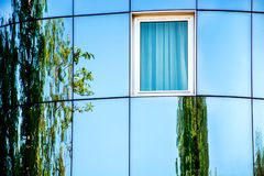 Abstract modern oval facade with glass and reflection of green tree stock photography