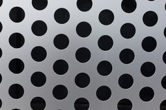 Black circles on a metal surface pattern texture background stock images