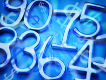 Abstract Money and Numbers Background. A montage of metal numbers and dollar symbols on a blue background Royalty Free Stock Photos