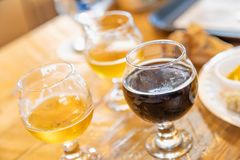 Abstract of Small Glasses of Micro Brew Beer Varieties On Bar. Abstract of Multi-colored Glasses of Micro Brew Beer Varieties On Bar stock image