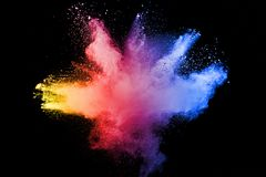 Abstract multicolored powder explosion on black background. Freeze motion of color dust  particles splash. Painted Holi Stock Image