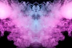 Abstract mystical bat silhouette straightened wings and head from streams of colorful smoke evaporating from a vape illuminated by. Neon lights on a black royalty free stock photography