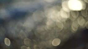 Abstract nature summer or spring ocean sea background. Small waves on water surface in motion blur with bokeh lights