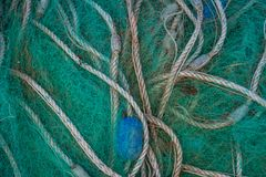 Abstract nautical image of a pile of old blue fishing net. That is twisted and frayed stock image