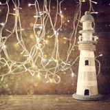 Abstract nautical lifestyle concept. old vintage lighthouse on wooden table and warm gold garland lights. vintage filtered image w Stock Images