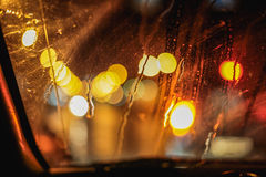 Abstract night city light and bokeh through car windscreen covered in rain, background stock photo