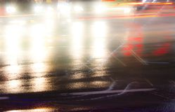 Abstract night traffic on rainy city street. Blurry night traffic on rainy city streets intersection with light trails and reflections on wet asphalt Royalty Free Stock Photos