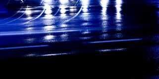Abstract night traffic on rainy city street. Blurry night traffic on rainy city streets intersection with light trails and reflections on wet asphalt Royalty Free Stock Photo
