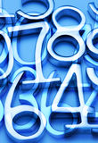 Abstract Number Background Math. A montage of metal numbers on a blue background Royalty Free Stock Photography