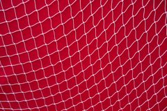 Abstract nylon fishing net background. Nylon fishing net stretched across red background wall royalty free stock images