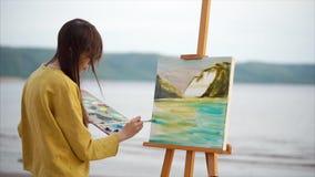Abstract oliebeeld van landschap en vrouwelijke schilder op het werk Creatieve persoon stock videobeelden