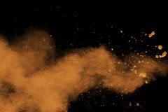Abstract orange dust explosion on  black background. Abstract orange powder splattered on black background, Freeze motion of orange powder splash Royalty Free Stock Images