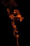 Abstract orange smoke-like shape against black Stock Photography