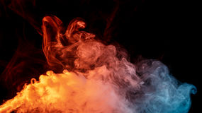 Abstract orange turquise smoke Weipa. Abstract smoke Weipa. Personal vaporizers fragrant steam. The concept of alternative non-nicotine smoking. Orange turquise Stock Images