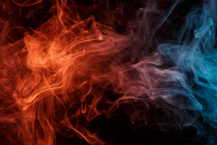 Abstract orange turquise smoke Weipa. Abstract smoke Weipa. Personal vaporizers fragrant steam. The concept of alternative non-nicotine smoking. Orange turquise Royalty Free Stock Photos