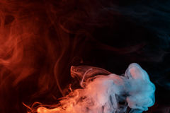Abstract orange turquise smoke Weipa. Abstract smoke Weipa. Personal vaporizers fragrant steam. The concept of alternative non-nicotine smoking. Orange turquise Royalty Free Stock Image