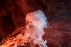 Abstract orange turquise smoke Weipa. Abstract smoke Weipa. Personal vaporizers fragrant steam. The concept of alternative non-nicotine smoking. Orange turquise Stock Photo