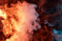 Abstract orange turquise smoke Weipa. Abstract smoke Weipa. Personal vaporizers fragrant steam. The concept of alternative non-nicotine smoking. Orange turquise Royalty Free Stock Photo