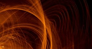 Abstract orange, yellow, gold light glows, beams, shapes on dark background Royalty Free Stock Photos